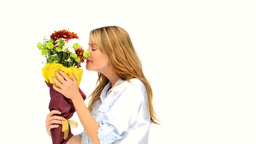 Casual blonde woman smelling a bunch of flowers Stock Video Footage