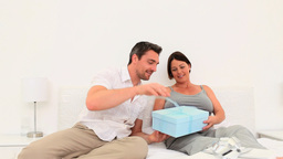 Man giving a gift to his pregnant wife Stock Video Footage