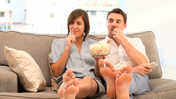Couple watching tv with popcorn Footage