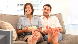Young couple watching tv with popcorn Footage