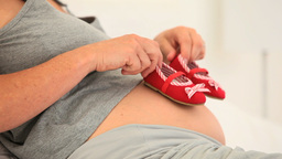 Pregnant woman holding little shoes Stock Video Footage