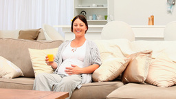 Pregnant woman drinking a glass of orange juice Footage