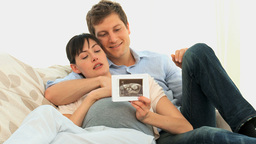 Couple looking at the scan of their future baby Stock Video Footage