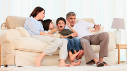 Family watching a movie with popcorn Stock Video Footage