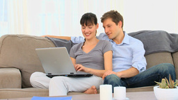 Attractive couple using a laptop Stock Video Footage