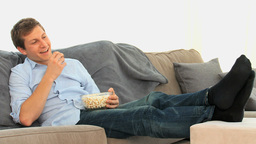 Man eating popcorn in front of tv Footage