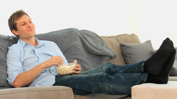 Man eating popcorn in front of tv Stock Video Footage