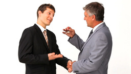 Businessman giving keys to an other man Footage
