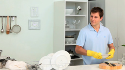Handsome man doing the dishes Footage
