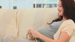 Smiling pregnant woman knitting Stock Video Footage