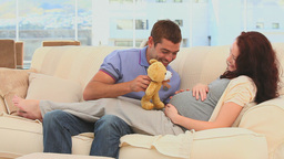 Future parents playing with a teddy bear Footage