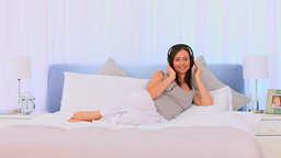 Beautiful woman listening to some music on her bed Footage