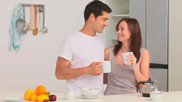 Couple drinking a cup of coffee in the kitchen Footage