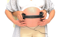 Man putting headphone on the belly of his pregnant Footage