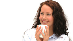 Woman drinking a cup of coffee against a white bac Stock Video Footage