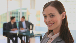 Businesswoman looking at the camera while her team Stock Video Footage