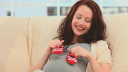 Pregnant woman playing with baby shoes Footage