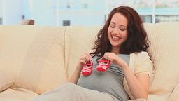 Pregnant woman playing with baby shoes on the sofa Footage