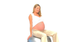 Pregnant woman doing streches against a white back Stock Video Footage