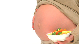 Pregnant woman holding a bowl of greens Footage