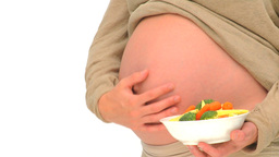 Pregnant woman holding a bowl of greens Stock Video Footage