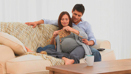 Pregnant woman knitting with her husband Stock Video Footage