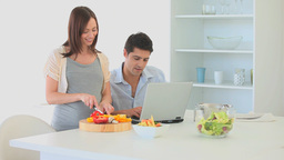 Pregnant woman cooking while her husband working on his... Stock Video Footage