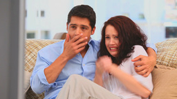 Couple watching a scary movie Stock Video Footage