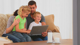 Cute family looking at a laptop Stock Video Footage