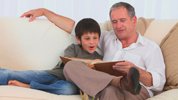 Boy looking at an album with his grandfather Stock Video Footage