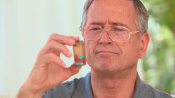 Mature man looking at his pills Footage