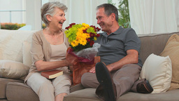 Cute elderly couple with a bunch of flowers Stock Video Footage
