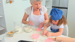Grandmother baking with her grand daughter Stock Video Footage