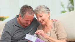 Retired man offering a gift to his wife Stock Video Footage