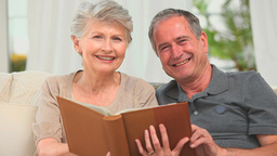 Retired couple looking at an album Stock Video Footage