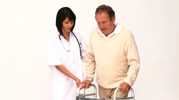 A nurse helping her patient to use a walker Footage