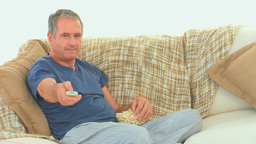 Mature man watching tv with popcorn Stock Video Footage