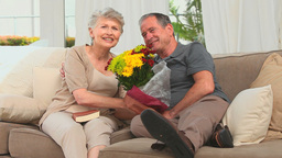 Retired couple holding a bunch of flowers Stock Video Footage