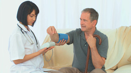 A nurse taking the blood pressure of her patient Stock Video Footage