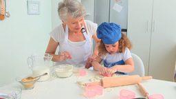 Grandmother baking cookies with her grand daughter Footage