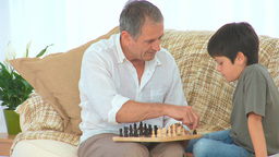 Little boy learning to play chess Stock Video Footage