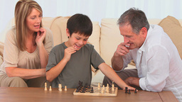 Grandmother helping her grandson to play chess Stock Video Footage