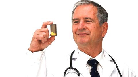 Elderly doctor holding yellow pills Footage