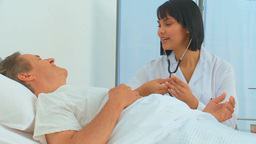 A nurse using a stethoscope on her patient Footage
