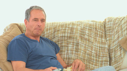 Mature man watching tv with popcorn Footage
