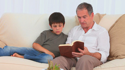 Casual man reading a book with his grandson Footage
