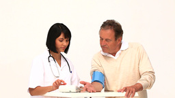 A nurse taking the blood pressure of her patient Footage