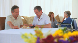 Men playing chess while their wives talking to eac Stock Video Footage