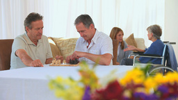 Men playing chess while their wives talking to eac Footage