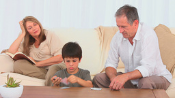 Little boy dealing cards to his grandfather Footage